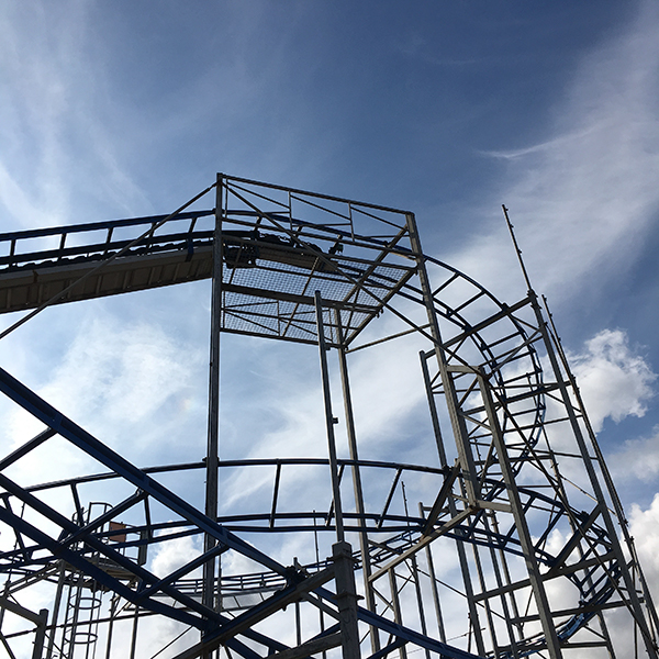 detail view of rollar coaster against a blue sky with clouds